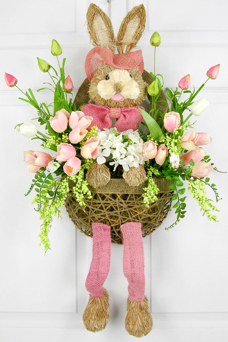 A sweet bow-tied bunny arranged in a woven half basket with a handle perfect for any place you want a little touch of Easter fun. The basket is filled with pink and white tulips, ferns and berries. Me