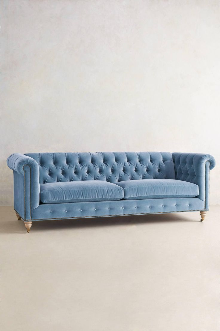 How to Decorate with Pantone's Rose Quartz and Serenity - Velvet Lyre Tufted Chesterfield Sofa in Light Blue, $2498; at Anthropologie