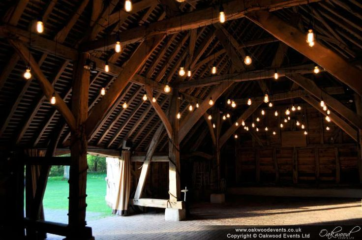 Canopy of edison bare bulbs with authentic bakelite holders and squirrel filaments. Gorgeous barn wedding lighting by #oakwoodevents