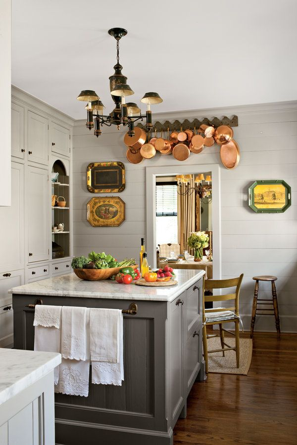 A small but efficient island holds refrigerator drawers and a bookcase for cookbooks. Painted deep gray to contrast with the lighter color of the cabinets and topped with marble, it feels vintage and perhaps even original to the house. At the end sits an antique tea table where the couple eats breakfast.