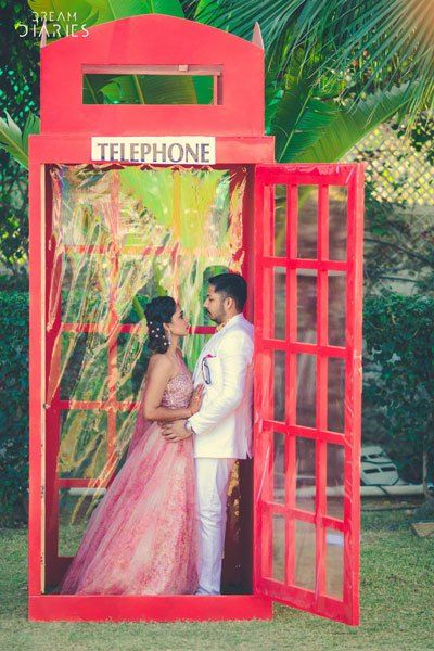 Red telephone booth photo op for indian wedding| couple photoshoot ideas | Indian bride in pretty pink gown | Indian wedding photo booth ideas | Photo Op ideas | The ultimate guide for the Indian Bride to plan her dream wedding. Witty Vows shares things no one tells brides, covers real weddings, ideas, inspirations, design trends and the right vendors, candid photographers etc.| #bridsmaids #inspiration #IndianWedding | Curated by #WittyVows - Things no one tells Brides | www.wittyvows.com