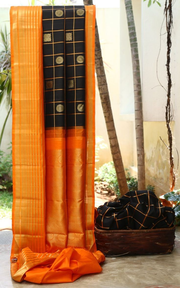 BLACK CHECKERED KANCHIVARAM WITH GOLD ZARI BHUTTAS IS OFFSET BY A BRIGHT ORANGE AND GOLD BORDER. THE SIMPLE ORANGE AND GOLD PALLU GIVES THE SAREE A BEAUTIFUL FINISH