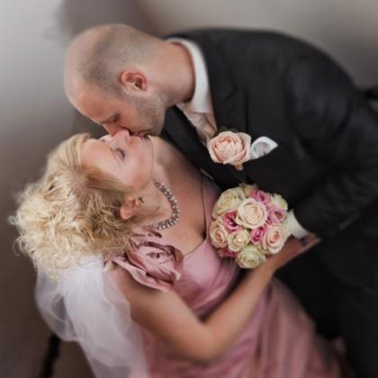 Bruidspaar met bruidsboeket roze en crème rozen