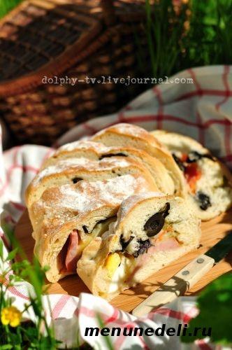Отрезаный кусочек готового хлеба для пикника с ветчиной помидорами сыром маслинами вареными яйцами и базиликом