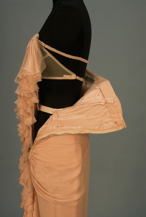 "Jean Desses strapless chiffon evening gown, mid 20th century. Asymmetrical pink crinkled silk sheath with ruching and left side triple ruffle opening into a hem ruffle that lengthens toward back, boned bodice with sewn-in bra, side zipper. Label ""Jean Desses 12. R d.pt. Champs-Elysees. Paris"""