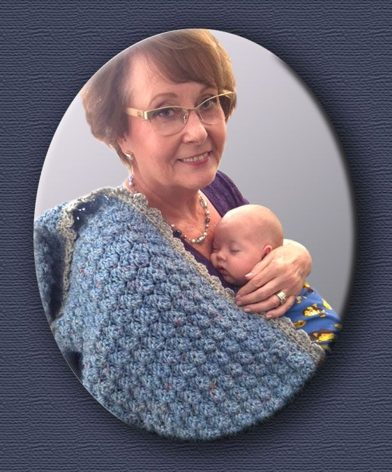 Crocheted baby blanket for baby boy. Grandma showing off your beautiful new grandson.