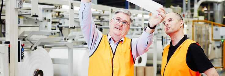 Two men in orange vests in a factory inspecting a strip of fabric or paper.