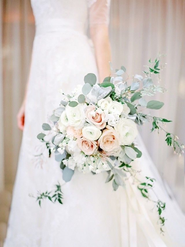 Cascading all-white bouquet  with a mixture of roses, ranunculus, peonies, and silvery eucalyptus