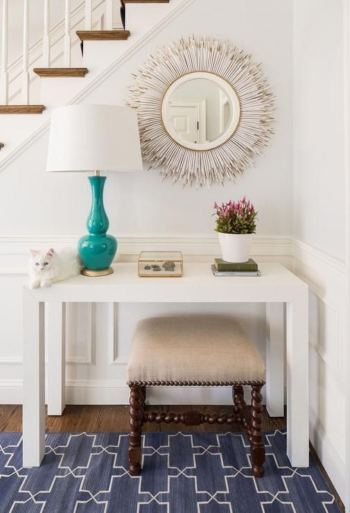 Chic foyer features a staircase wall clad in wainscoting lined with a West Elm Parsons Table topped with a turquoise lamp and a Janice Minor White Porcupine Quill Mirror alongside a Madeline Weinrib rug.
