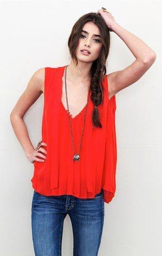 Mooie losvallende rode top, strakke jeans, lange, maar simpele ketting erbij. Door het materiaal toch chiq.