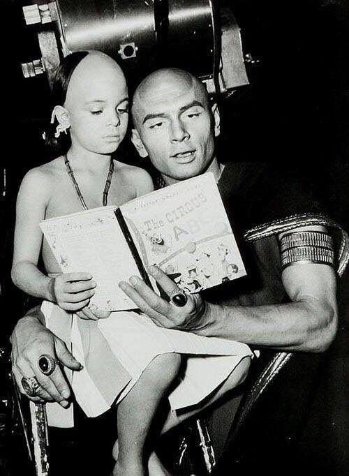 Yul Brynner reading to his son on the set of The Ten Commandments.