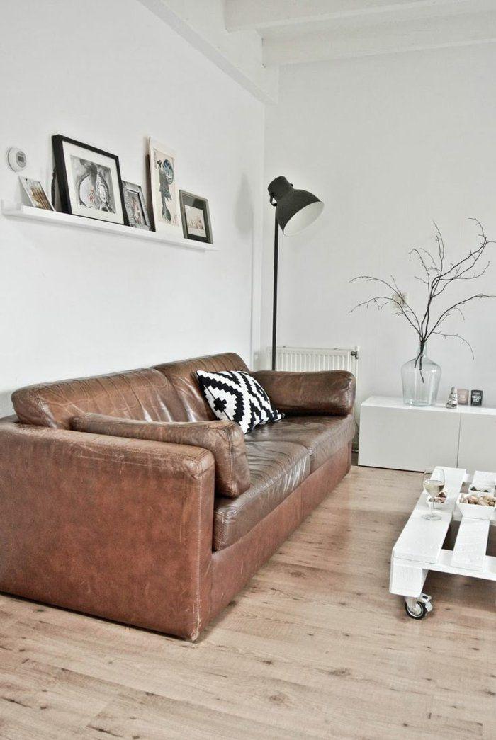 fauteuil club pas cher en cuir marron et sol en parquette avec murs blancs et une petite table basse en bois