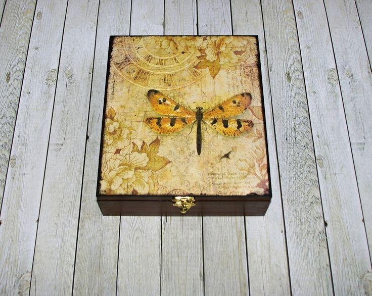 Čajová+s+motýlem+Dřevěná+krabička+na+čaj+(či+cokoliv+jiného+-vyndávací+přihrádky)+o+rozměrech+cca+21,5x24,5+cm+a+výšce7,5+cm.+Krabička+je+natřena+akrylovými+barvami,+ozdobená+technikou+decoupage+(rýžový+papír),+lehce+patinovanáadoplněná+zápínáním.+Následně+přetřena+lakem+s+atestem+na+hračky.+Uvnitř+nechána+přírodní.