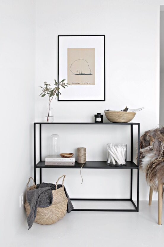 earthy and artful corner with black shelving, woven basket, fur throw, hanging art, white walls