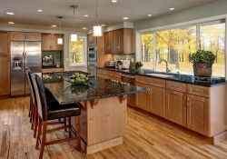 Photo gallery of remodeled kitchen features CliqStudios Dayton Maple Caramel cabinets and large center island