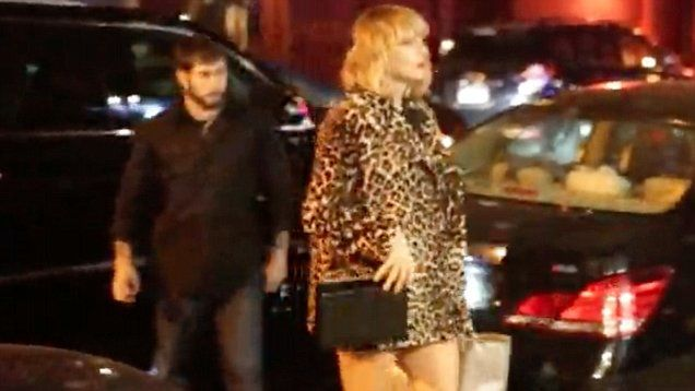 'Trump or Hillary?' Taylor Swift bombarded with q's about who she's voting for in New York. Wearing a leopard print coat and black strappy heels, she showed off her incredibly long legs. She wore bright red lipstick.
