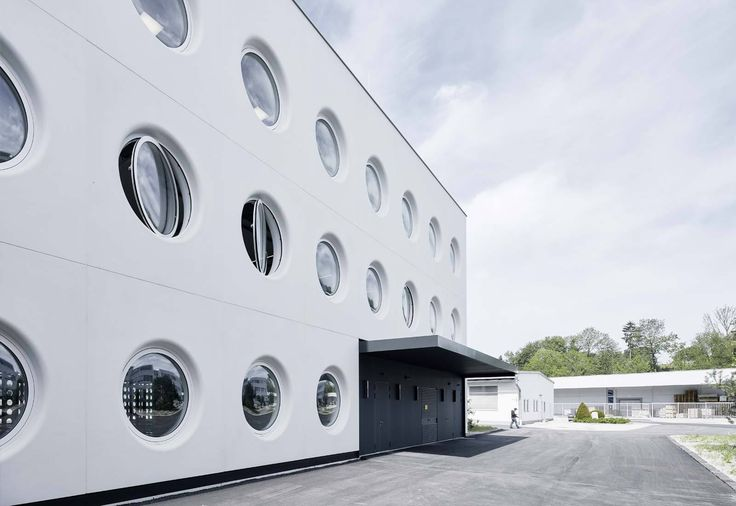 Silhouette Lens Lab is a minimalist architecture project located in Linz, Austria, designed by X Architects. The facility is a production and warehouse center characterized by an array of circular windows that pivot open horizontally. One side of the building's facade features a wall of smaller circular openings that playfully interact light with shadow when viewed upon from the inside.