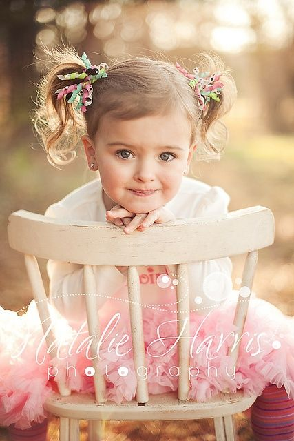 Cute girl in a pink tutu dress, on a chair and with ribbon curls in her pigtails