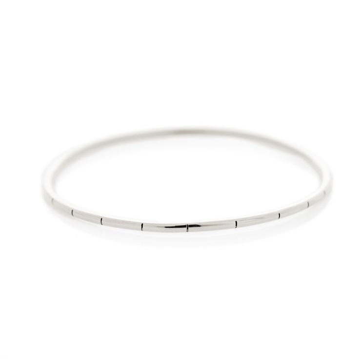 A thin stripy sterling silver bangle with rounded edges. (Please note that each stripe is hand etched and therefore can vary in pattern.)