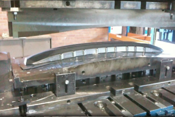 Die press for the manufacture of a metal bumper for a Toyota Camry. The picture shows the female half of the die/mould raised away from the male. The metal part is still on the lower mould/die and you can seen the excess that needs trimmed away after pressing.
