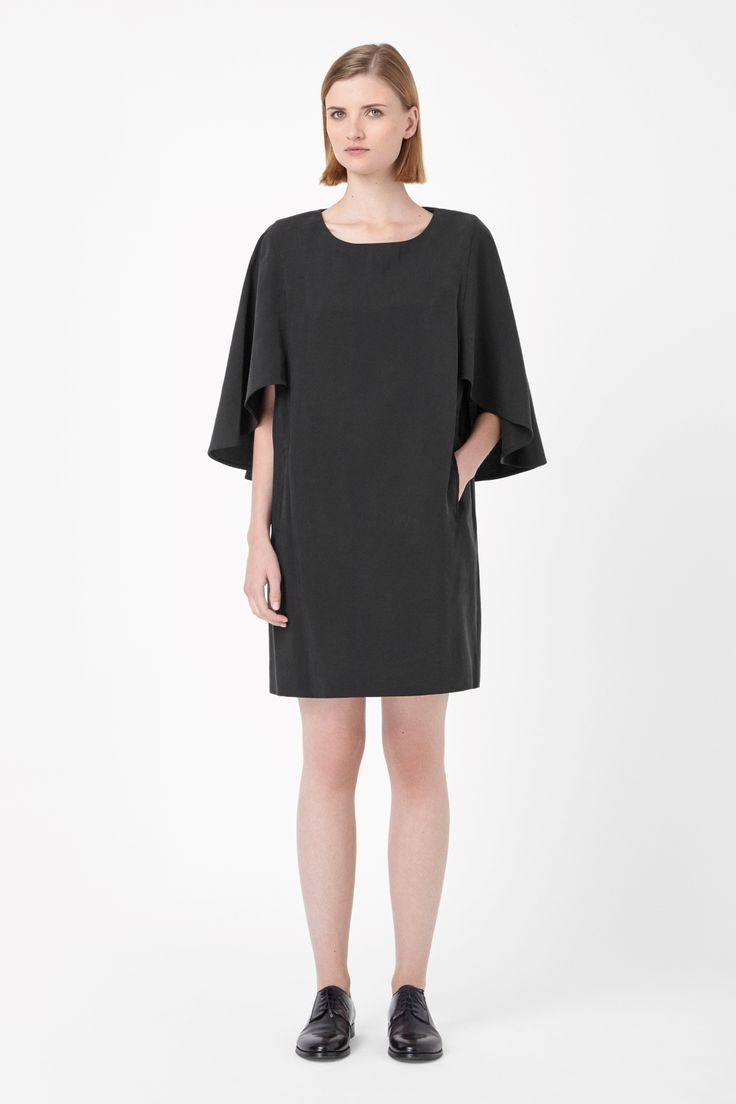 Made from a fluid fabric with a soft finish, this dress has a round layer across the sleeves and back for a modern cape effect. A loose fit with relaxed proportions, it has a wide round neckline, two welt front pockets and a clean straight hemline.