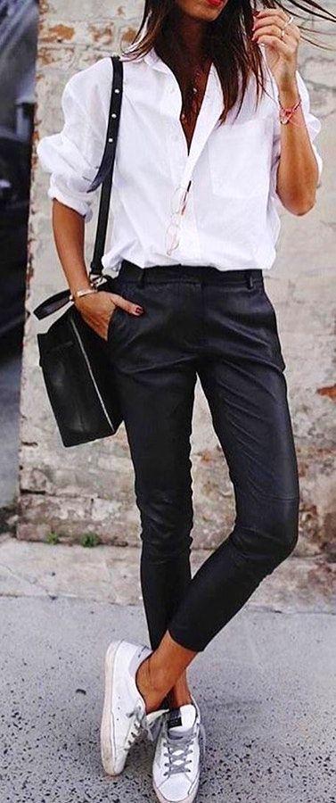 Frau in weißem Businesshemd mit schwarzen engen Hosen und einem Paar