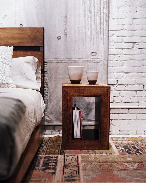 Bedroom Photo - A wooden side table and bed atop a patterned rug