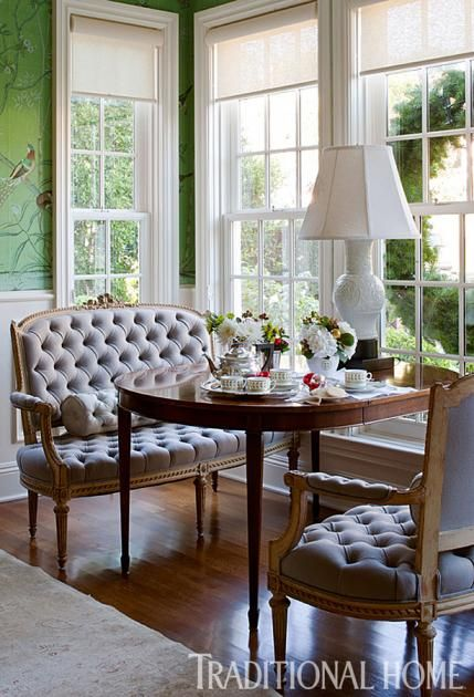 A pretty pair of tufted Louis XV settees flank an antique English table and provide a lovely spot to sip on coffee. - Traditional Home ® / Photo: Michael Garland / Design: Emily Sullivan