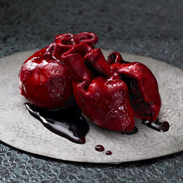 """UK-based rock n' roll baker, Lily Vanilli, gives us this edible bleeding heart cake, this ghoulish creation is made of red velvet sponge cake, cream cheese frosting, and blackcurrant and cherry """"blood"""" that's sure to get your heart pumping."""