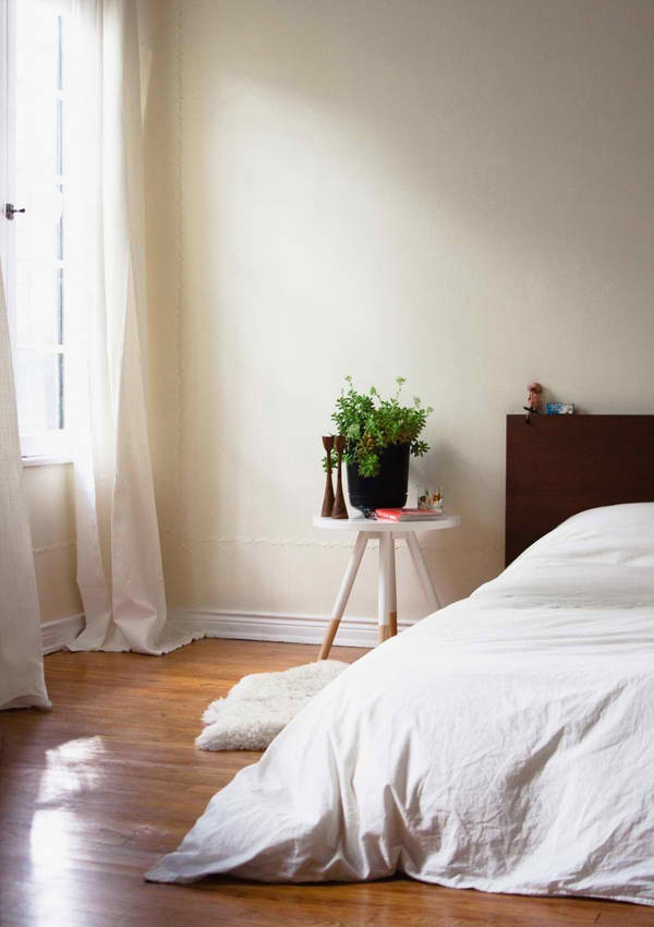 Minimalist bedroom. There's too much clutter around the bed, though. Just the plant would be perfect.