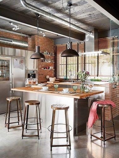 Une ambiance loft new-yorkais s'invite dans cette cuisine ! Le style industriel est apporté par les accessoires en métal tels que les tabourets et les deux suspensions vintage.  Le plan de travail de l'îlot en bois clair réchauffe la pièce tandis qu'au plafond les poutres et tuyauteries acier ancrent encore plus cette cuisine dans le style indus'. La modernité n'est pas pour autant mise de côté, elle est d'ailleurs relevé par l'inox qui compose à la fois le corps de l'îlot de cuisine, la…