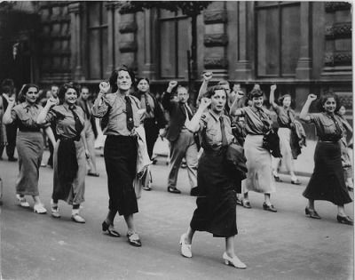 Spain - 1936. - GC - Spanish women parade down the street rendering the leftist salute.