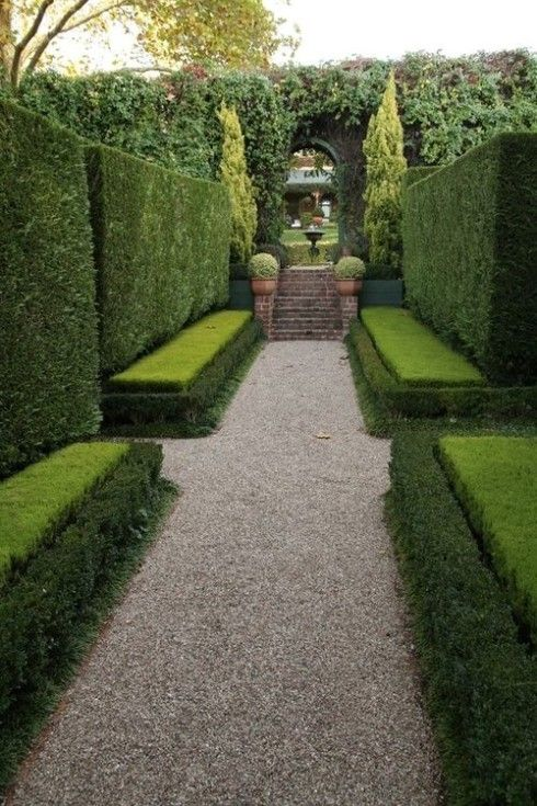 Tall clipped hedges with low hedges trimmed to resemble benches. Love the two shades of green and the topiaries in pots beside the stairs. N...