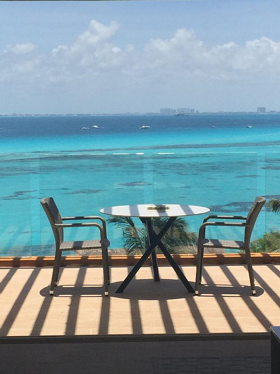 View from  condo balcony. Water dark spots are coral. Cancun skyline in distance
