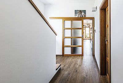Kuchyň z amerického ořechu zhotovil na míru truhlář z Českých Budějovic. Z tohoto krásného materiálu vyrobil i dveře, stolek a police a elegantní prosklené posuvné dveře ze vstupní haly.