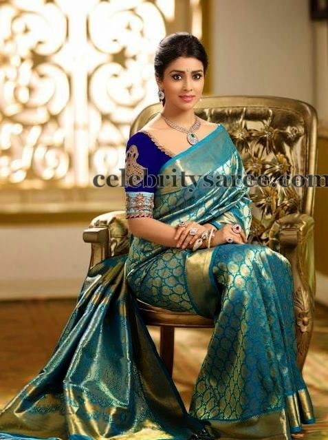 South Indian actress Shriya wearing green and gold colors combination kanjivaram silk saree with gold sari weave rich border, paisley des...