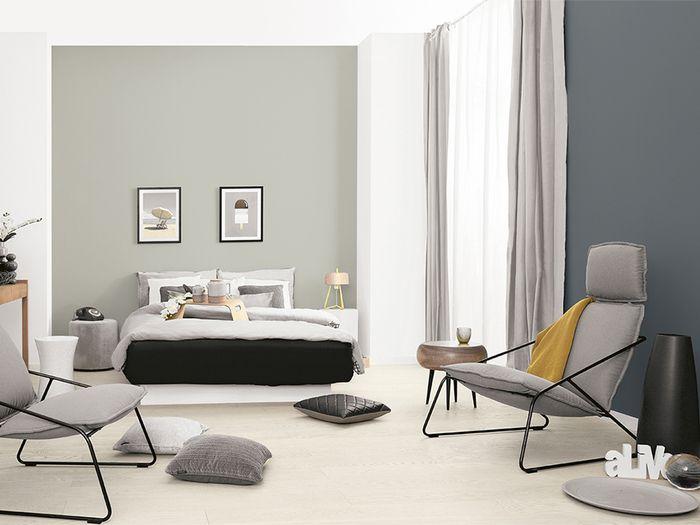 Z pozoru surowy wystrój sypialni nabiera nowoczesnego charakteru w połączeniu z metalicznymi, czarnymi akcentami. Sposobem na urozmaicenie i ocieplenie aranżacji są subtelne akcenty w naturalnej barwie drewna. / Tikkurila Color Now - paleta TRUE (szarości)