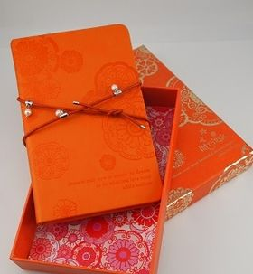 Pearl Wrap Journal in Tangerine by Intrinsic. Encased in a colour-matching box, which features luscious gold foiling, the embossed journal within is wrapped with a leather and pearl strap that can also be worn around your wrist as a stunning bracelet.