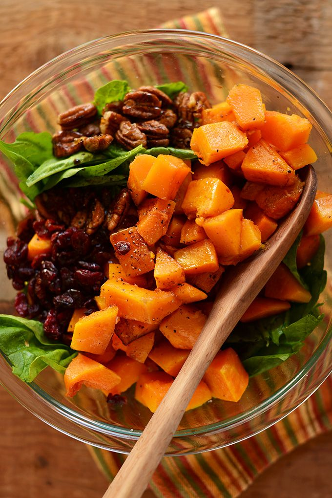 A warm salad made with roasted butternut squash, cranberries, spinach and candied pecans. Healthy, filling and a perfect take-along lunch or side at fall and holiday gatherings.