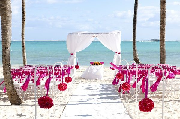 4 Breathtaking Beach Wedding Setups: This pretty-in-pink setup is the definition of eye-catching. Situated on the famed Bavaro Beach, the flirty floral pomanders and free-flowing chair ribbons really pop against the sugary white sand! #beach #wedding