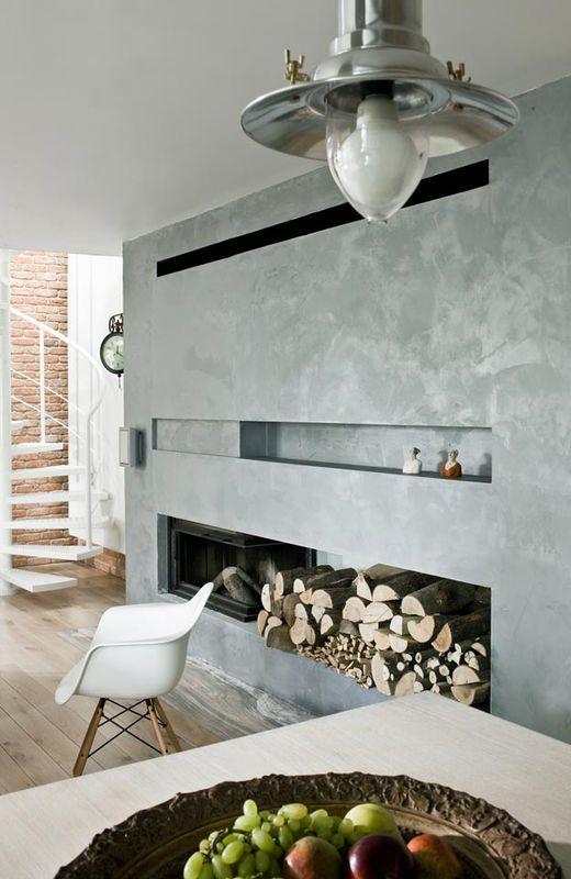 Najważniejszym punktem tego mieszkania jest kominek. Widać go z salonu, kuchni, jadalni, a nawet z pomieszczeń na piętrze. Co ciekawe, osiągnięto to przy wykorzystaniu minimum środków dekoracyjnych i zachowując prostotę formy / The stylishly designed industrial interior with a fireplace.