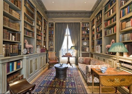 Blue antique oriental rug, muted green library shelves with white trim in London townhouse.
