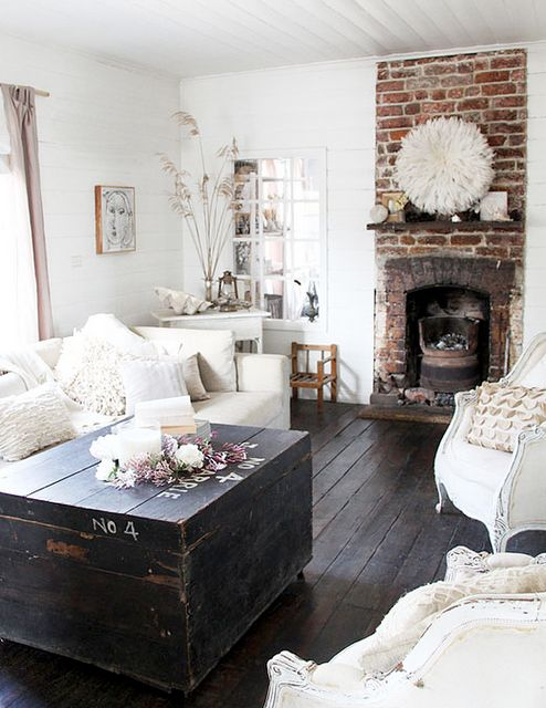more exposed brick and white furniture. i love the dark coffee table chest however.