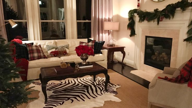 Christmas themed Living Room. William Sonama tartan, Pottery Barn Woody pillow, William Sonoma Home white linen sofa, Wayfair chair, Ballard tartan throw, zebra rug over sisal, West Elm round mirror. Design by Evans Construction and Design