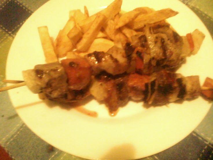 anticuchos de pavo y patatas fritas.