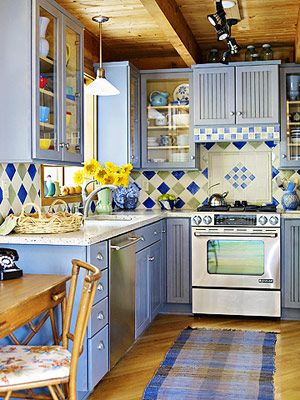 Concrete countertop, blue cabinets, and colorful tile backslash.