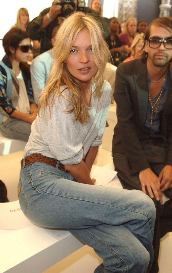 Kate Moss wearing white top, tan belt and jeans on the frow
