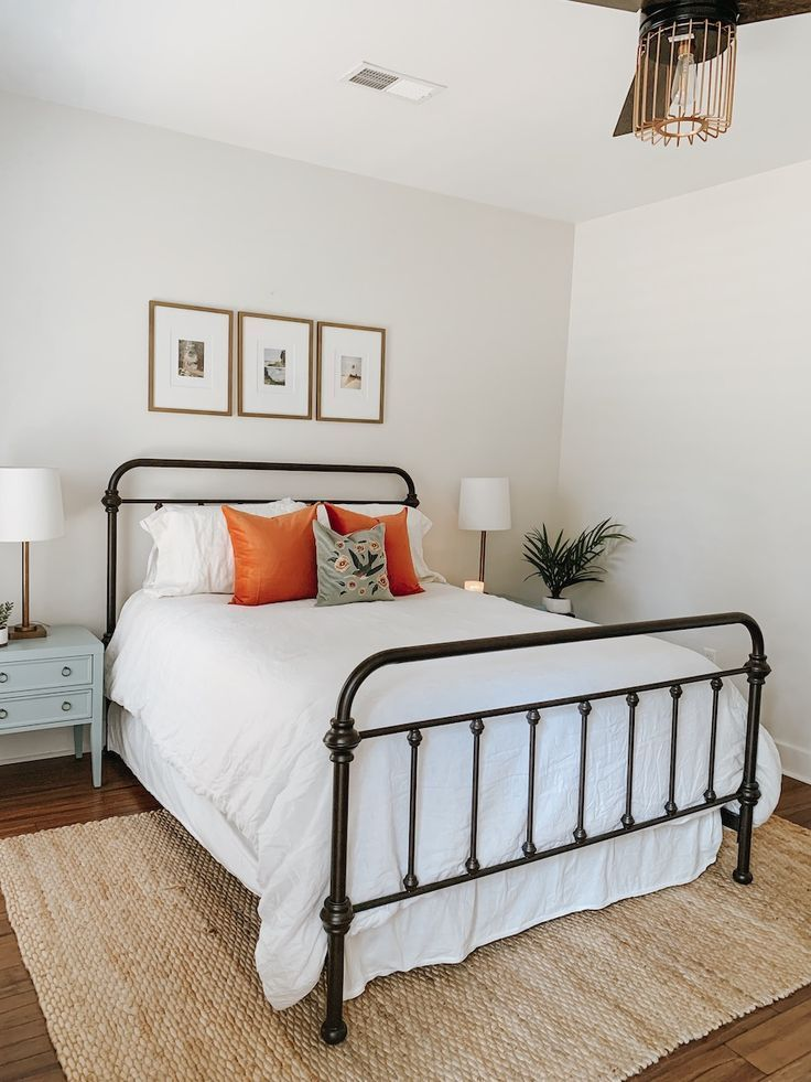 Minimalist bedroom with orange and gray pillows, white comforter, and brown ratt…