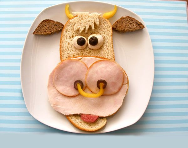 moo!  ● 1 slice dark bread for ears, two slices of light for face and mouth ~ cut one slice about 1 / 3 from the crust, to create and another small section for the  hair. ● large slice of ham and two small round - nose. ● black olives - pupils and nostrils. ● Mushrooms - the eyes.  ● yellow pepper - the horns and nose ring.