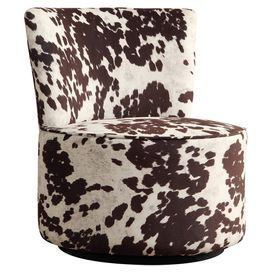 """Add a touch of midcentury-chic style to your den or living room decor with this swiveling accent chair, showcasing a wood frame and cowhide-inspired upholstery.   Product: ChairConstruction Material: Cow hide, high density foam and woodColor: Brown and whiteFeatures: Armelss design is a space-saver Swivel seatDimensions: 32"""" H x 28"""" DiameterNote: Assembly requiredCleaning and Care: Use professional cleaning materials and a clean cloth"""